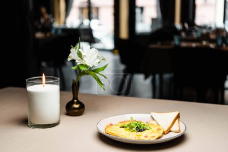 Photo for Plate with omelet and toasts for breakfast on table with candle and flowers in cafe - Royalty Free Image