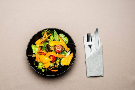 top view of salad in plate with fork and knife on table