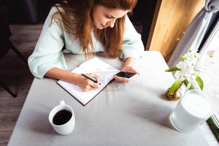 attractive woman using smartphone and writing in notepad in cafe with cup of coffee
