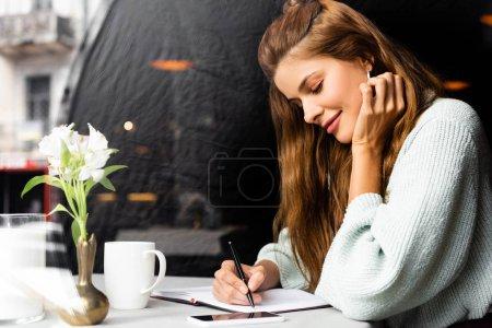 Photo pour Attrayant femme heureuse écriture dans le bloc-notes dans le café avec smartphone et tasse de café - image libre de droit