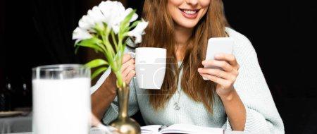 Photo pour Vue recadrée de femme souriante avec tasse de café en utilisant smartphone dans le café - image libre de droit