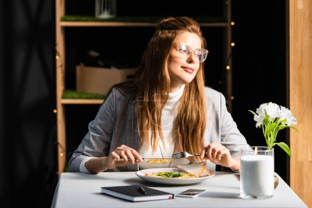 Photo for Beautiful woman eating breakfast in cafe with notepad and smartphone - Royalty Free Image