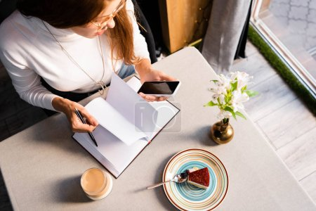 Photo for Overhead view of woman with notepad using smartphone in cafe with cake, coffee and flowers - Royalty Free Image
