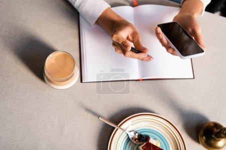 Photo pour Vue partielle de la femme avec bloc-notes en utilisant smartphone dans le café avec gâteau et café - image libre de droit