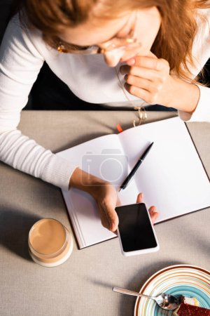 overhead view of woman with notepad using smartphone in cafe with glass of coffee