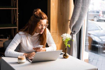 Photo pour Redhead femme étudiant en ligne avec smartphone et ordinateur portable dans le café - image libre de droit