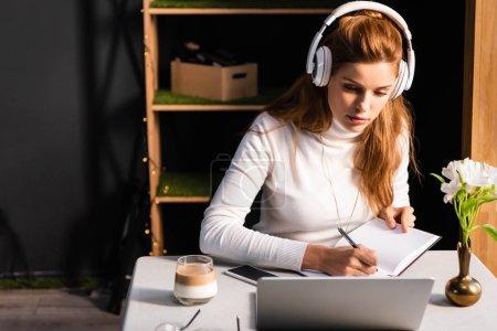 Photo pour Belle femme à tête rouge dans les écouteurs en écrivant dans le bloc-notes tout en regardant webinaire sur ordinateur portable dans le café - image libre de droit