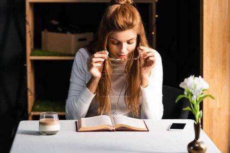 Photo pour Attrayant rousse femme avec smartphone et verre de livre de lecture de café dans le café - image libre de droit