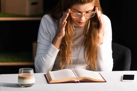 Photo pour Belle rousse femme livre de lecture dans le café avec smartphone et verre de café - image libre de droit