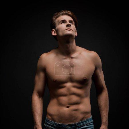 Photo pour Bel homme sexy posant isolé sur noir - image libre de droit
