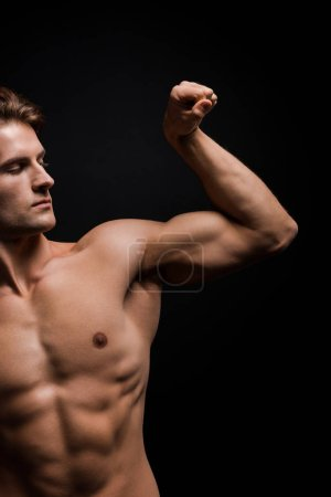 Photo for Handsome shirtless man showing muscles isolated on black - Royalty Free Image