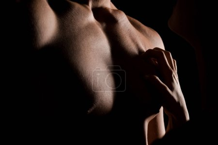 Photo for Cropped view of seductive couple hugging together, isolated on black with backlight - Royalty Free Image