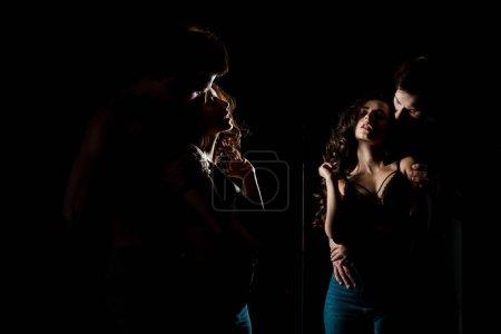 Photo pour Beau couple passionné étreignant et posant devant le miroir - image libre de droit