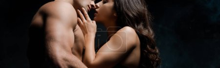 Photo for Beautiful seductive couple hugging and kissing, isolated on black - Royalty Free Image