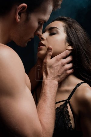Photo for Passionate man hugging and kissing beautiful girl, isolated on black - Royalty Free Image