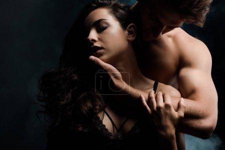 Photo pour Séduisant homme câlin belle fille, isolé sur noir - image libre de droit