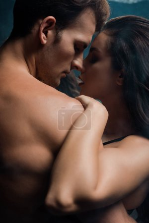 Photo for Beautiful passionate couple hugging in black room with smoke - Royalty Free Image