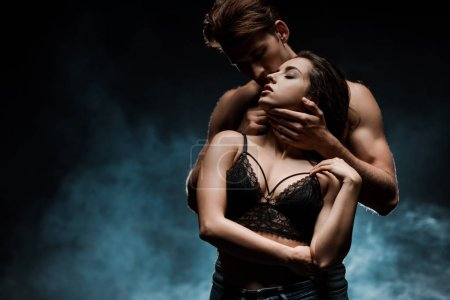Photo for Sensual couple hugging in black room with smoke - Royalty Free Image