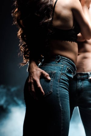 Photo pour Crochet vue d'un couple sexy blotti dans une pièce noire avec de la fumée - image libre de droit
