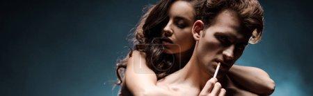 Photo pour Belle femme sexy embrassant homme fumant la cigarette dans une pièce obscure avec de la fumée - image libre de droit