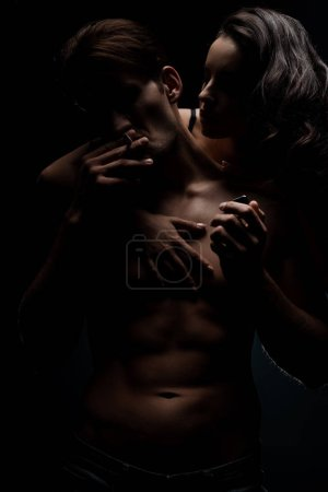 attractive woman hugging seductive man smoking cigarette, isolated on black