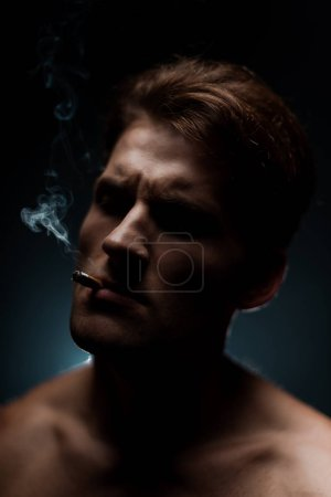 Photo for Handsome sexy man smoking cigarette in dark room - Royalty Free Image