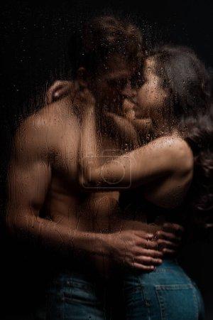 Photo pour Un couple passionné embrassant et embrassant derrière un verre mouillé - image libre de droit