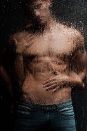 Photo pour Femme passionnée embrassant un homme sans chemise derrière un verre mouillé - image libre de droit