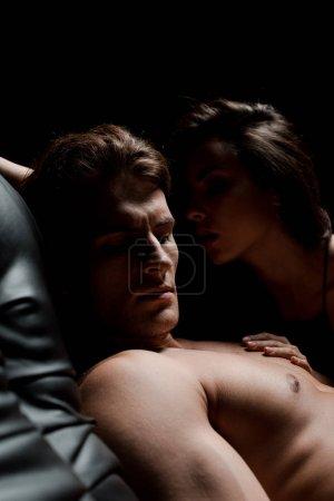 Photo pour Beau couple séduisant assis sur canapé dans la chambre noire - image libre de droit