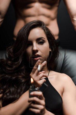 Photo pour Un couple d'adultes assis sur un canapé dans une pièce sombre, alors qu'une femme sexy fume la cigarette - image libre de droit