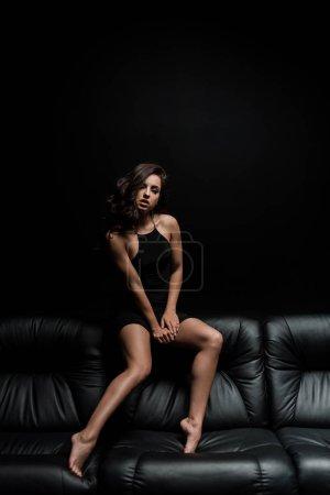 Photo pour Belle sensuelle posant sur un canapé dans une pièce noire - image libre de droit