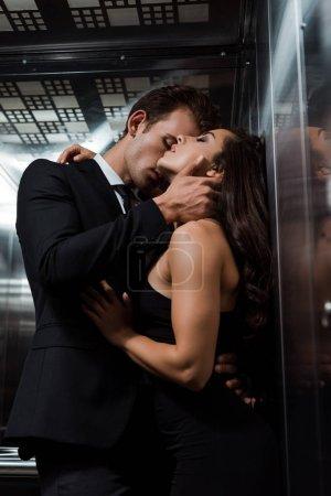 Photo pour Bel homme embrassant et embrassant belle femme sexy dans l'ascenseur - image libre de droit