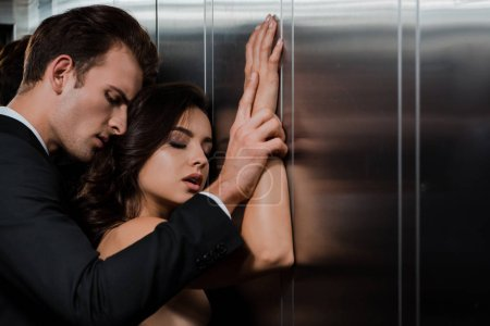 Photo for Handsome man hugging sexy woman from back in lift - Royalty Free Image