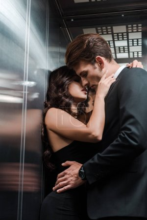 Photo for Beautiful seductive couple hugging and kissing in lift - Royalty Free Image
