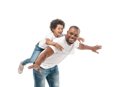 Photo pour Happy african american man piggybacking adorable son and imitating flying on white background - image libre de droit