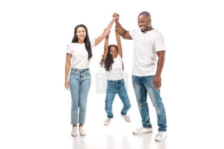 Photo pour Enfant africain américain gai suspendu aux mains de ses parents sur fond blanc - image libre de droit