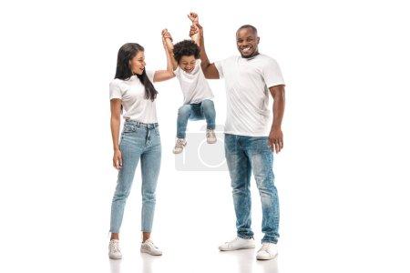 Photo pour Un garçon américain africain gai s'accroche aux mains de ses parents sur un fond blanc - image libre de droit