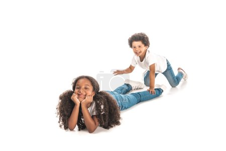 Photo for Cheerful african american boy sneaking up to lying sister on white background - Royalty Free Image