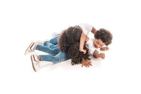 Photo pour Joyeux frère africain et soeur s'amuser tout en imitant la lutte sur fond blanc - image libre de droit