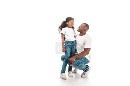 happy african american father squatting and talking to adorable daughter on white background