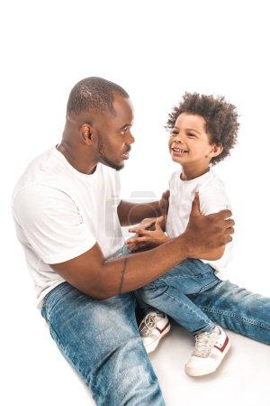 Photo pour Bel homme afro-américain parlant à un fils souriant sur fond blanc - image libre de droit