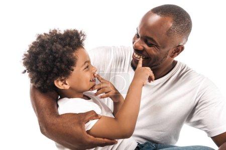 Photo pour Joyeux garçon afro-américain toucher son nez et le nez de père heureux isolé sur blanc - image libre de droit