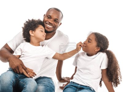 Photo pour Un garçon américain africain gai touche le nez de sa soeur assis sur les genoux de son père sur fond blanc - image libre de droit