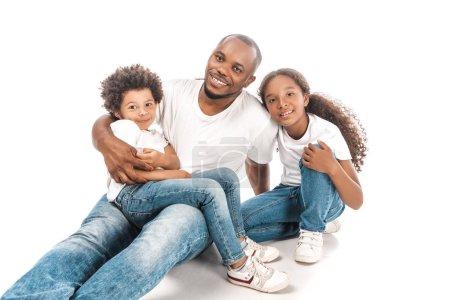 Foto de Feliz hombre africoamericano abrazando a su hijo e hija mientras se sentaba juntos sobre fondo blanco. - Imagen libre de derechos