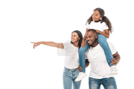Photo for Cheerful african american woman pointing with finger, and husband piggybacking adorable daughter isolated on white - Royalty Free Image