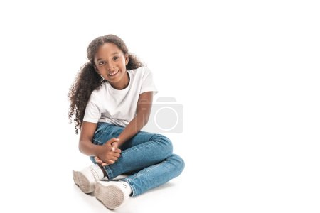 Photo for Cheerful african american child smiling at camera while sitting on white background - Royalty Free Image