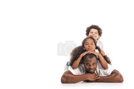 Foto de Hija e hijo africoamericano que se divierten mientras descansan en los padres juntos sobre fondo blanco. - Imagen libre de derechos