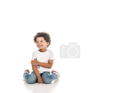 cheerful african american boy looking away while sitting on white background