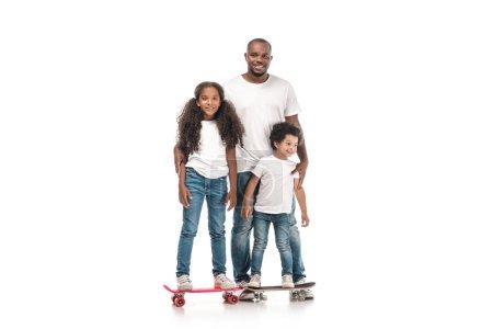 Photo pour Joyeux homme afro-américain près de fille debout sur skateboard, et fils sur penny conseil sur fond blanc - image libre de droit