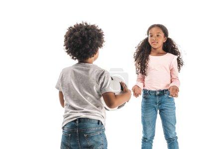 Foto de Vista trasera del niño africoamericano que sostiene balón de fútbol mientras se encuentra frente a la hermana aislada en blanco. - Imagen libre de derechos